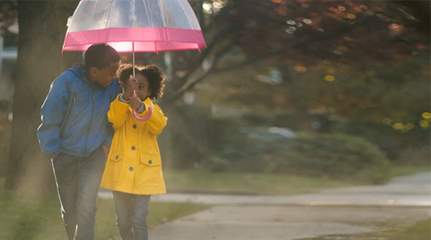 Child walking in rain with umbrella